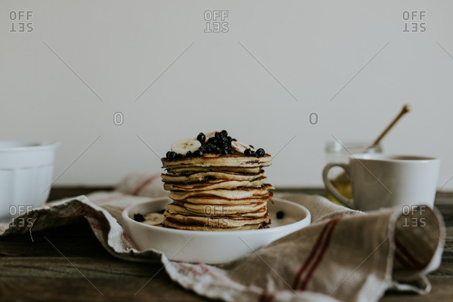 Stack of blueberry pancakes topped with berries and bananas on a table