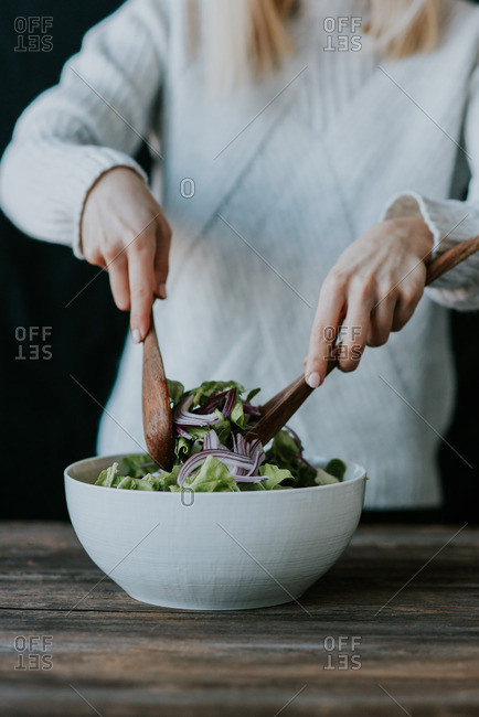 Woman mixing a salad with lettuce and onions