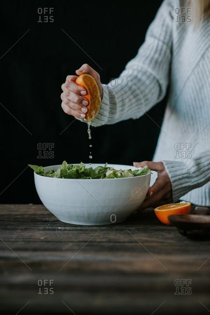 Woman squeezing orange juice into a salad
