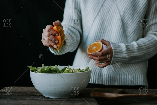 Woman squeezing orange juice into a bowl with lettuce