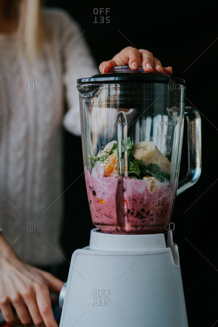 Woman mixing a smoothie in a blender