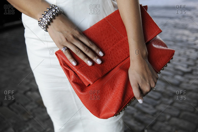 Woman wearing white holding a red clutch