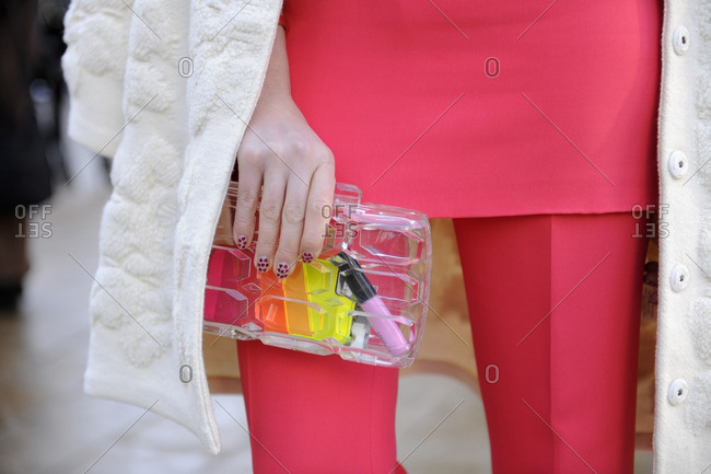 Fashionable woman holding a see through clutch