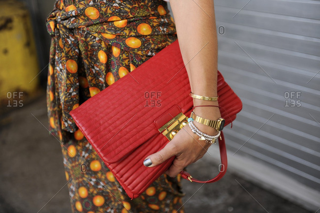New York, NY - October 10, 2016: Fashionable woman holding a red clutch