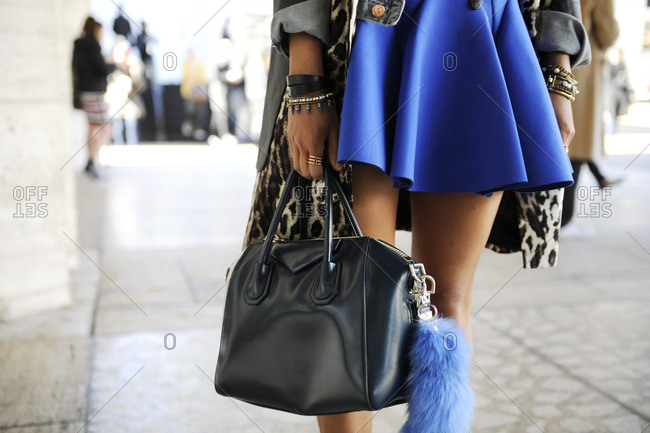 Woman in blue skirt holding a black purse