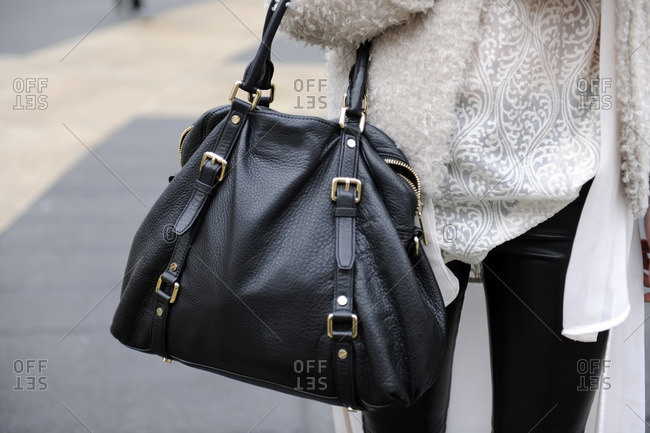 Woman wearing a white sweater holding a black purse