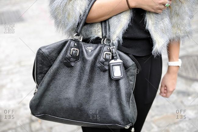 Woman wearing fur holding a black purse