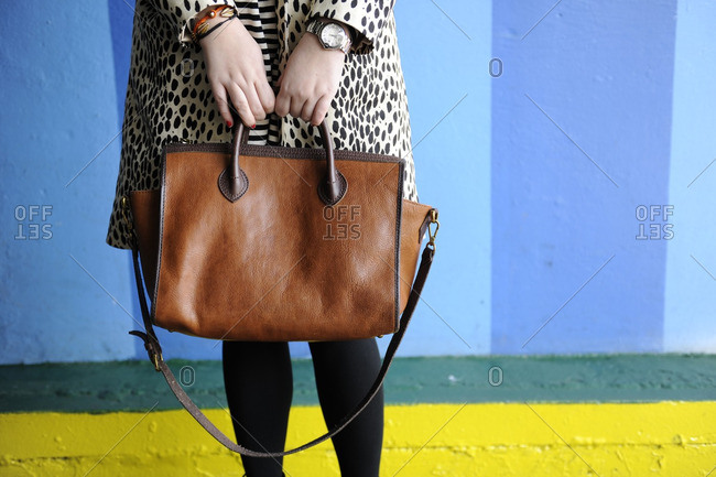 Woman in animal print holding a brown leather purse