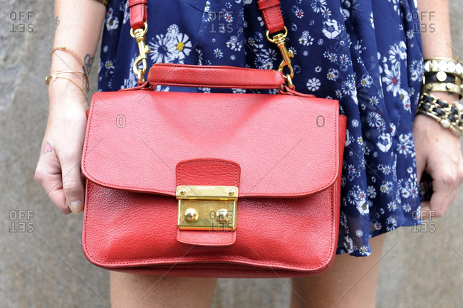 Fashionable woman holding a red purse