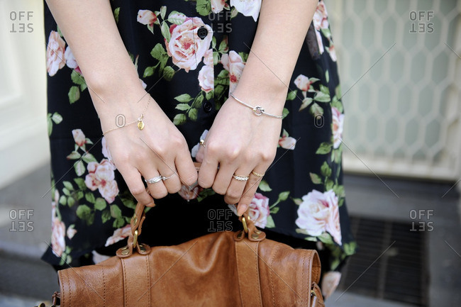 Woman in floral print dress holding a brown leather bag