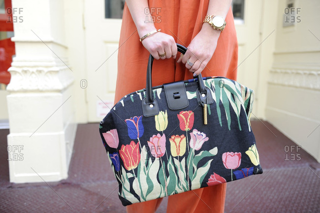 Woman holding a purse with a tulip pattern