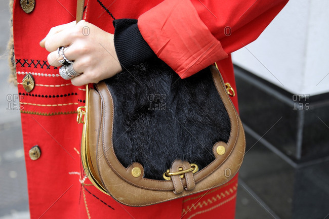 New York, NY - October 10, 2016: Woman in red with small fur pocketbook