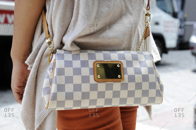 New York, NY - October 10, 2016: Woman with white and grey checkered purse