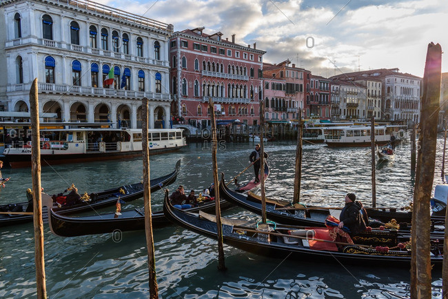 Venice, Italy - December 29, 2016: People riding gondolas in canal