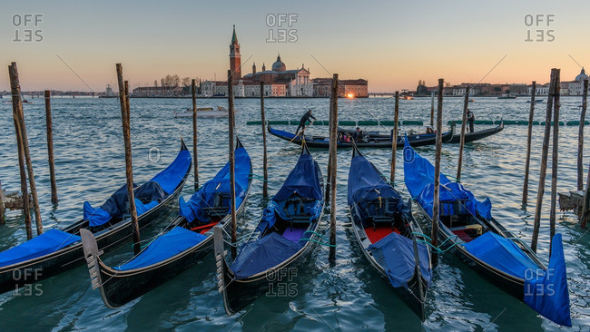 Venice, Italy - December 30, 2016: Gondolas in sunset near basilica