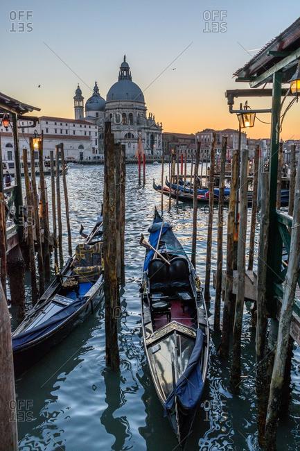Venice, Italy - December 30, 2016: Gondolas in sunset near a basilica
