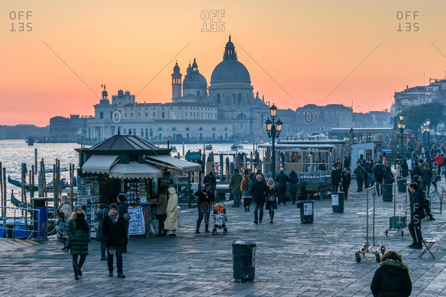 Venice, Italy - December 31, 2016: Crowds along waterfront in sunset