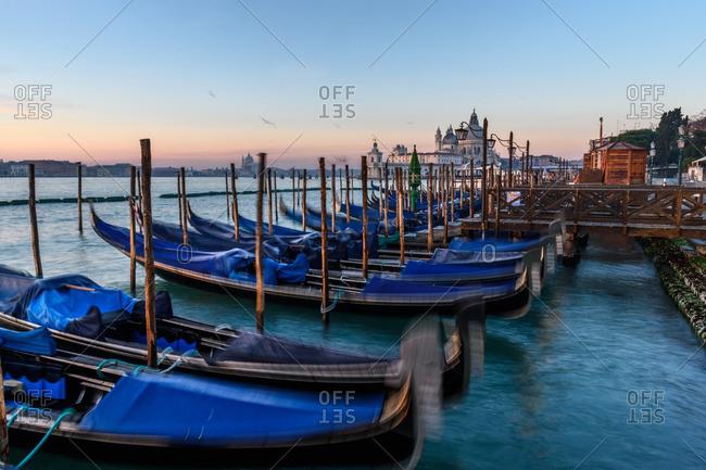 Venice, Italy - January 1, 2017: Gondolas and church in sunset, Venice