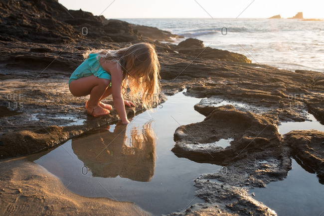 Little girl playing in a tidal pool on a beach
