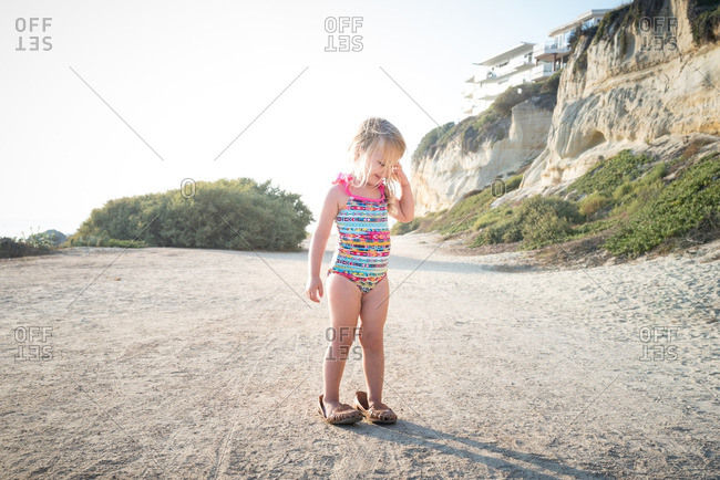 Little girl in oversized shoes standing on a beach