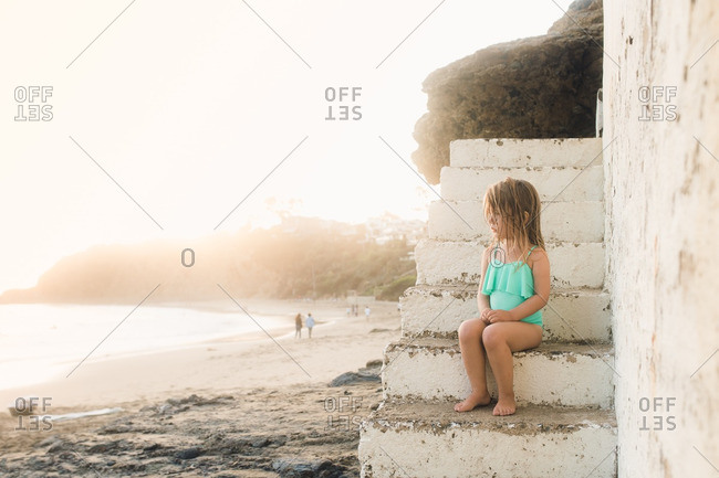 Little girl sitting on concrete steps overlooking a beach