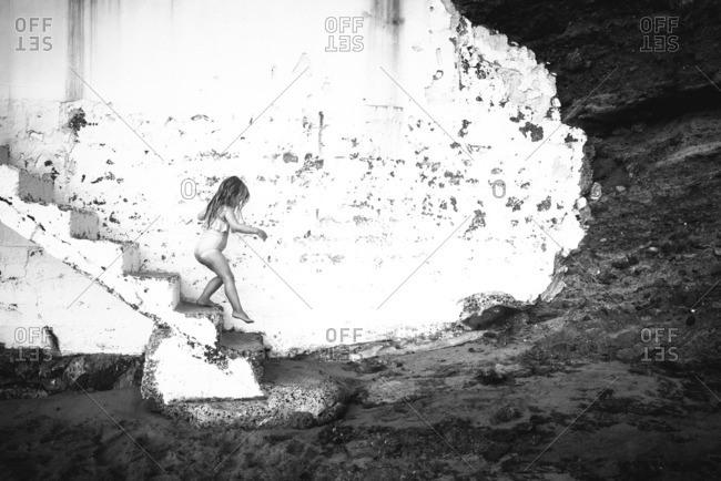 Little girl walking down concrete steps to a beach