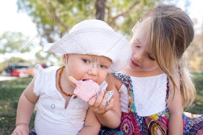 Little girl feeding her toddler sister an ice cream pop