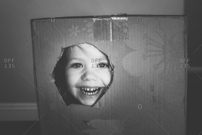 Little girl poking her face through a hole in a cardboard box