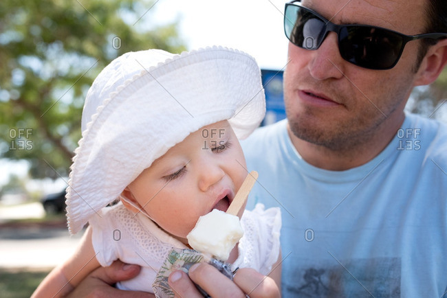 Father helping his toddler daughter eat a popsicle