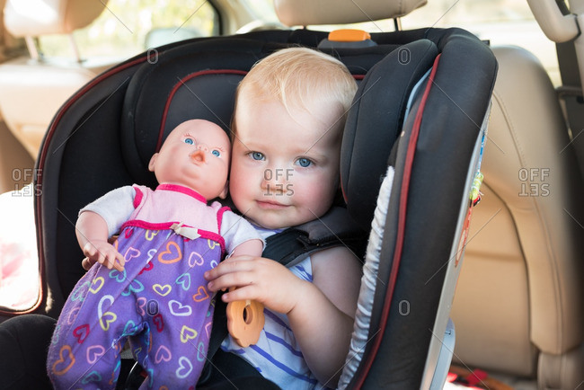 Toddler girl in a car seat holding a baby doll