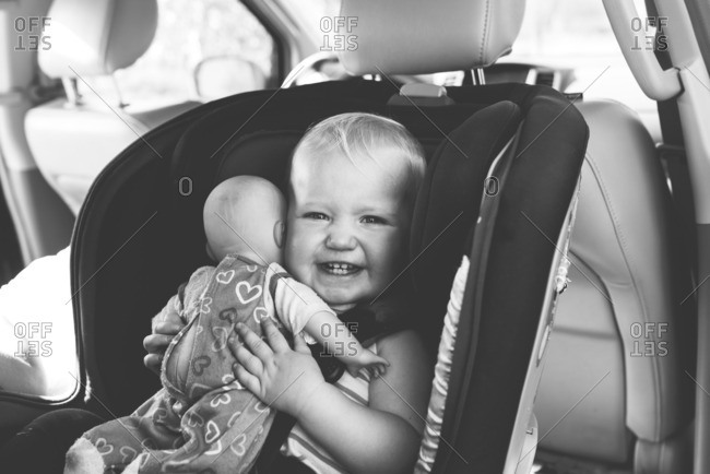 Little girl sitting in a car seat holding a baby doll