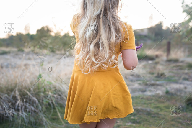 Little girl in a yellow dress walking in a field at sunset