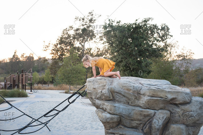 Girl in a yellow dress climbing on rocks at a playground