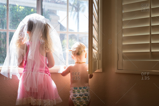 Two young sisters standing in a window looking outside