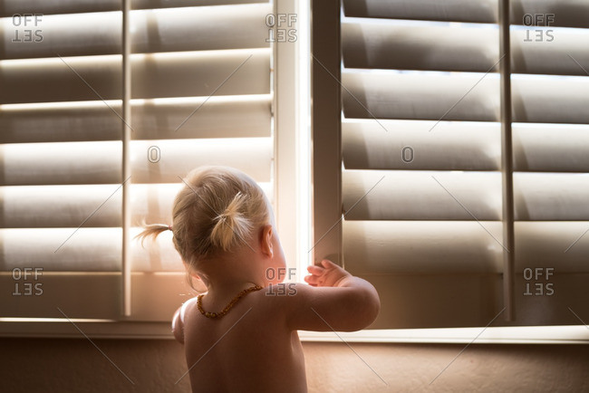 Toddler girl opening shutters on a window