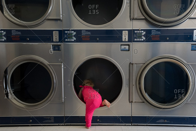 Toddler girl climbing into a washing machine at a Laundromat