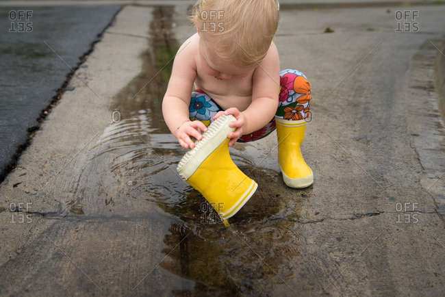 Toddler girl playing with her rain boot in a puddle