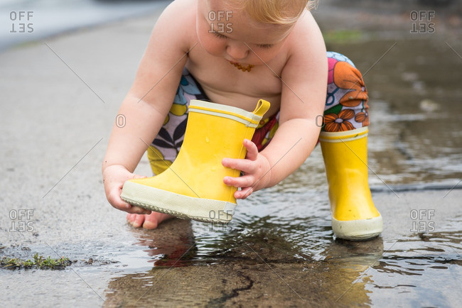 Toddler girl standing in a puddle playing with her rain boot