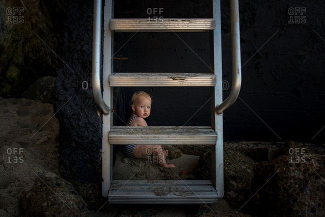 Toddler girl sitting behind a metal ladder on a beach