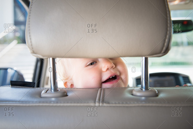 Little girl peering through a head rest in a car