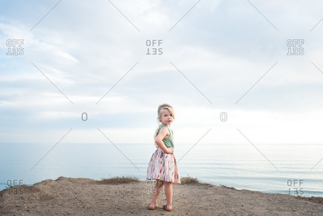 Little girl standing on a sandy cliff by the sea looking over her shoulder