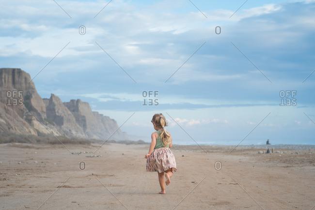 Little girl running on an empty beach beside cliffs