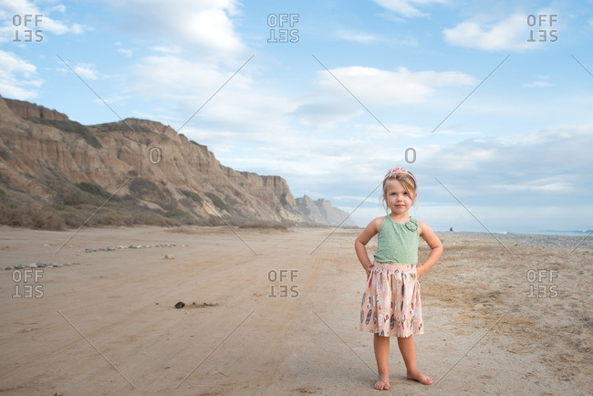 Little girl standing on a beach with her hands on her hips