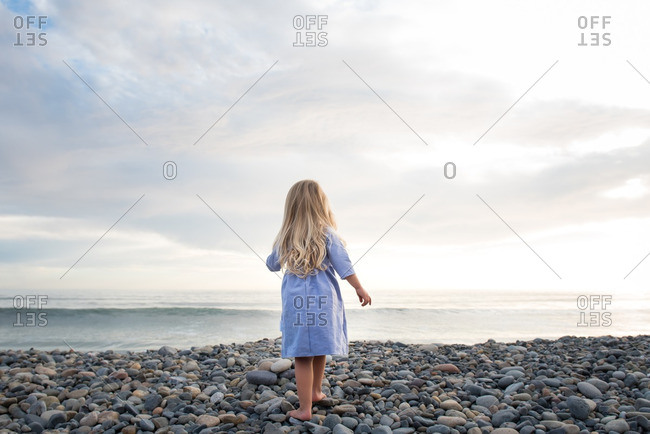 Little girl in a dress standing on a pebble beach