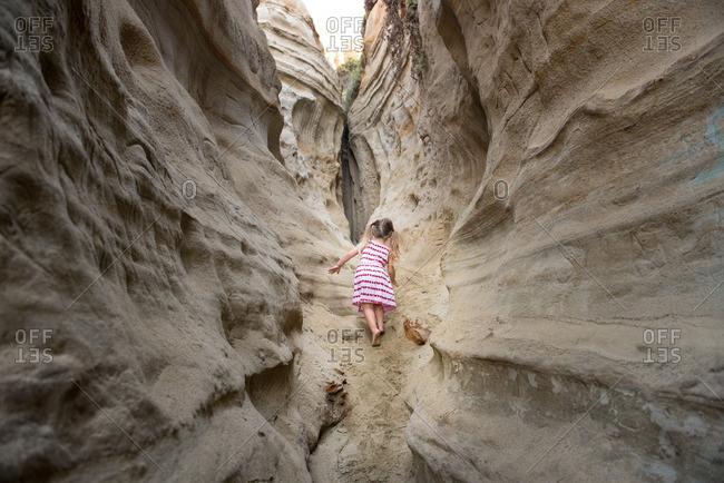 Little girl climbing in a narrow desert gorge