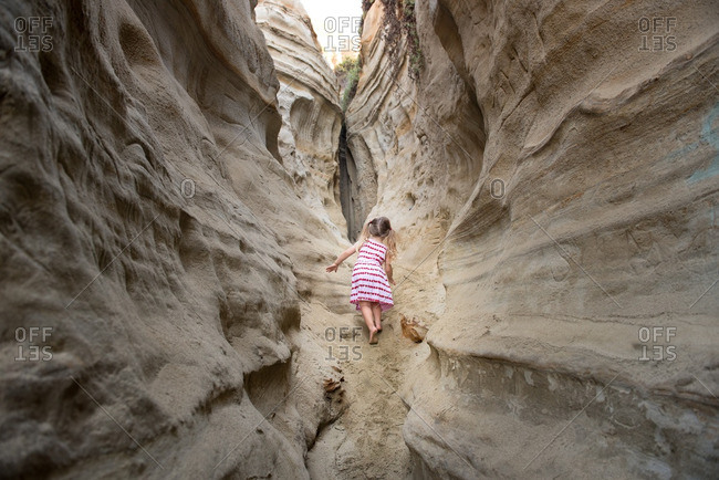 Little girl climbing in a narrow desert gorge
