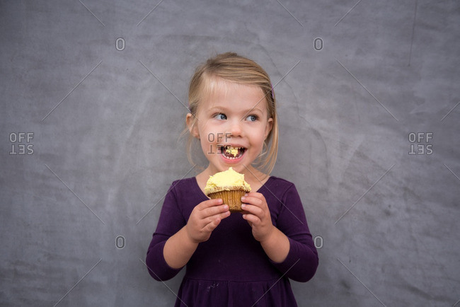 Little girl standing in front of a stone wall eating a cupcake