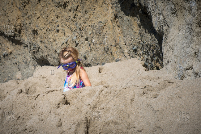 Little girl in goggles exploring rocks on a beach