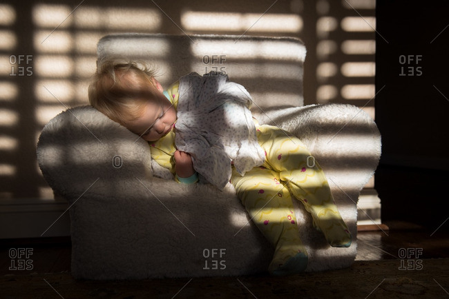 Toddler girl sleeping in a child's armchair near a window