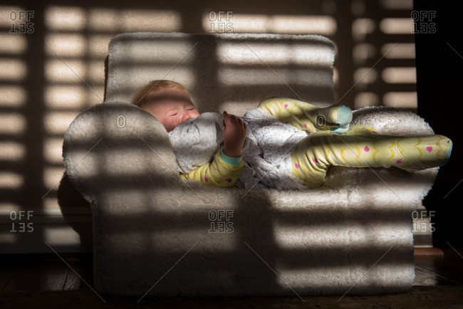 Toddler girl napping in a small armchair near a window